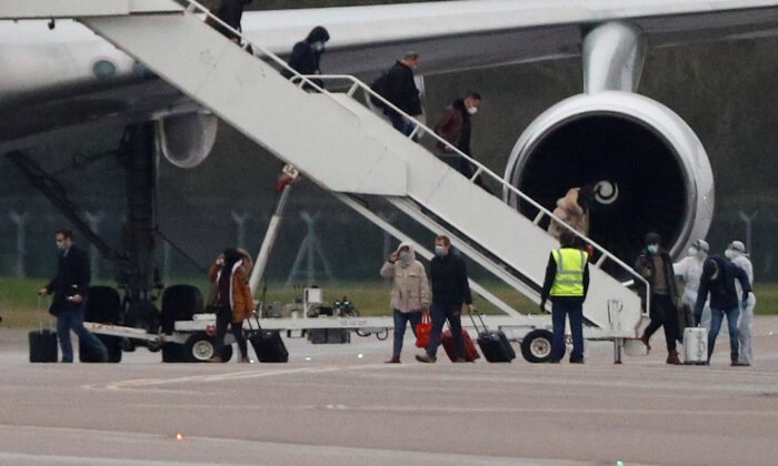 Passengers from China disembark from a plane at RAF Brize Norton near Oxford, United Kingdom, on Feb. 9, 2020. (Peter Nicholls/Reuters/File)