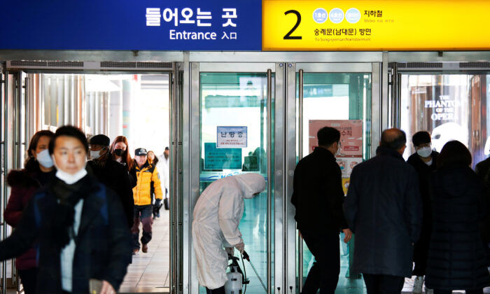 An employee from a disinfection service company sanitizes at the Seoul Railway Station in Seoul, South Korea, on Feb. 10, 2020. (Heo Ran/Reuters)