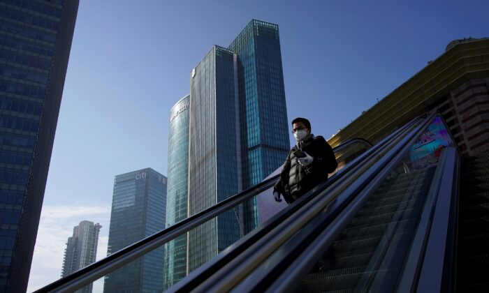 A man wearing a face mask rides an escalator at the Lujiazui financial district in Pudong, Shanghai, China on Feb. 10, 2020. (Aly Song/Reuters)