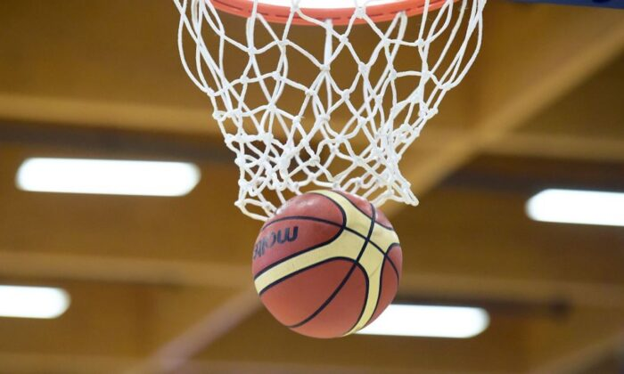 A basketball goes through a hoop in a 2017 file photo. (Nicolas Tucat/AFP/Getty Images)