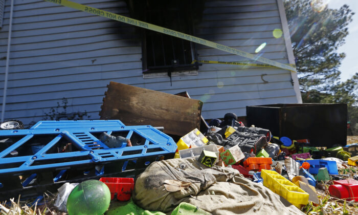 Burned children's clothing, furnishings exterior of a house at the scene of a fatal fire in Clinton, Miss., on Feb. 8, 2020. (Rogelio V. Solis/AP Photo)