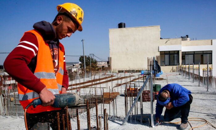 A construction worker saws steel rods at the site of a school that was funded by the U.S Agency for International Development (USAID) in Al-Jabaa, in the West Bank, on Jan. 22, 2019.  (HAZEM BADER/AFP via Getty Images)