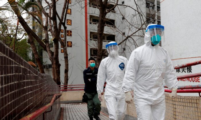Health workers in protective gears walk as they evacuate residents from a public housing building, following the outbreak of the novel coronavirus, outside Hong Mei House, at Cheung Hong Estate in Hong Kong, China on Feb. 11, 2020. (Tyrone Siu/Reuters)