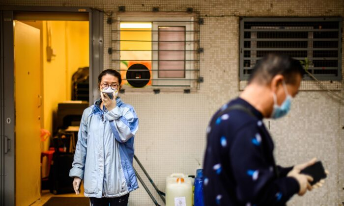 A woman wearing a face mask uses her phone next to containers of hydrogen peroxide in Hong Kong on Feb. 11, 2020. (Anthony Wallace/AFP via Getty Images)