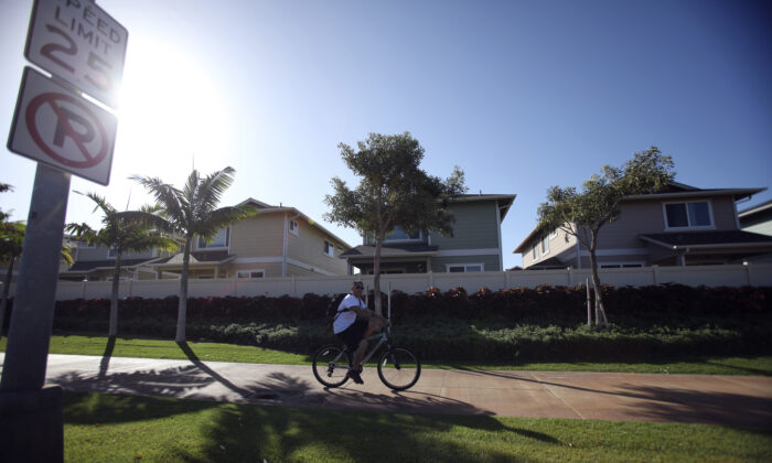A man cycles past the Trades housing division built by Gentry Homes in Ewa Beach, Hawaii, on March 6, 2013. (Hugh Gentry/Reuters)