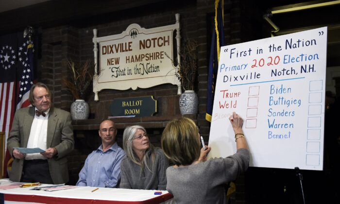 (L-R) Moderator Tom Tillotson, supervisor of the checklist Joe Casey, and town clerk Deborah Tillotson look on as Coralie Stepanian marks a Republican write-in vote on the board for Democratic candidate and former New York Mayor Michael Bloomberg during the presidential primary election midnight vote in Dixville Notch, New Hampshire, on Feb. 11, 2020. Three of the five votes went to Bloomberg. (Paul Hayes/Caledonian-Record via AP)