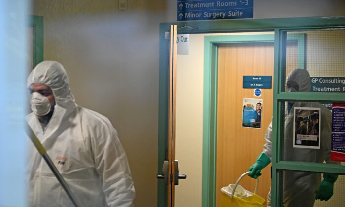 Workers dressed in protective clothing, including face masks and gloves, are pictured carrying buckets as they work inside Warmdene doctor's surgery at County Oak Medical Center in Brighton, United Kingdom, after it closed following reports a member of staff was infected with the Novel Coronavirus, on Feb. 10, 2020. (Glyn Kirk//AFP via Getty Images)