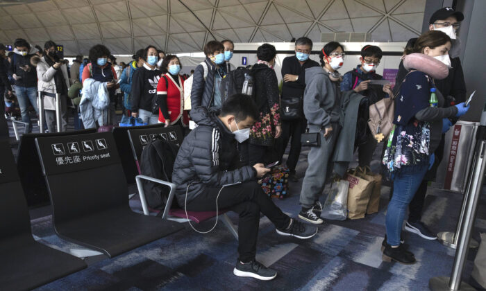 Masked passengers line up to board a flight for Beijing at the airport in Hong Kong on Feb. 9, 2020. (AP Photo/Ng Han Guan)