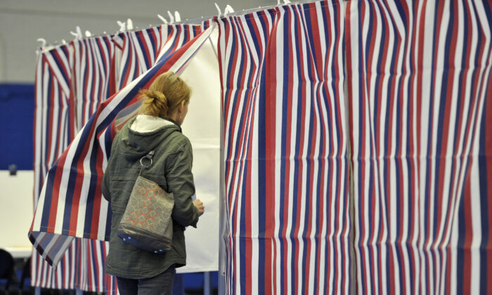 A woman enters a voting booth at the Ward Five Community Center during the New Hampshire primary in Concord, N.H., on Feb. 11, 2020. (Joseph Prezioso/AFP via Getty Images)
