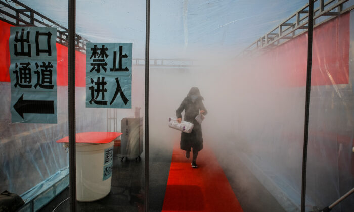 A woman wearing a face mask walks through a device that sprays disinfectant at an entrance to a residential compound, following an outbreak of the novel coronavirus in the country, in Tianjin, China on Feb. 11, 2020. (cnsphoto via Reuters)