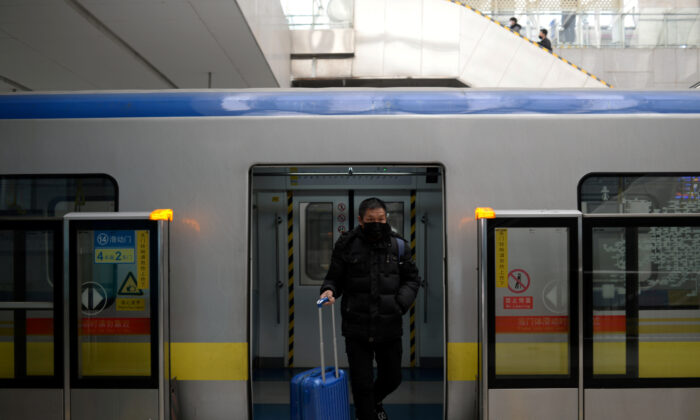 A man wearing a face mask walks out of the subway with a suitcase in the morning after the extended Lunar New Year holiday caused by the novel coronavirus outbreak, at the Xierqi subway station, in Beijing, China on Feb. 10, 2020. (ingshu Wang/Reuters)