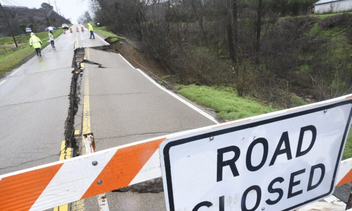 Mississippi Department of Transportation personnel is seen on scene where part of the roadway of Highway 80 has washed away just near Mount Alban Road in Vicksburg, Miss., on Feb. 11, 2020. (Courtland Wells/The Vicksburg Post via AP)
