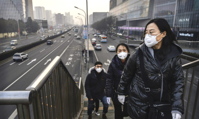 People wear protective masks as they cross a footbridge at a mall in Beijing on Feb. 11, 2020. (Kevin Frayer/Getty Images)