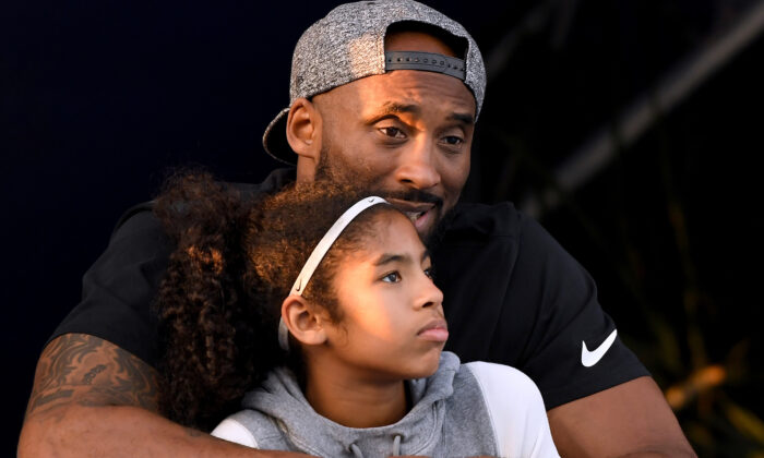 Kobe Bryant and daughter Gianna Bryant watch during day 2 of the Phillips 66 National Swimming Championships at the Woollett Aquatics Center, in Irvine, Calif., on July 26, 2018. (Harry How/Getty Images)