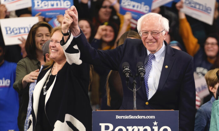Democratic U.S. presidential candidate Sen. Bernie Sanders (I-Vt.) is accompanied by his wife Jane O'Meara Sanders as he arrives to speak at his New Hampshire primary night rally in Manchester, New Hampshire, on Feb. 11, 2020. (Rick Wilking/Reuters)