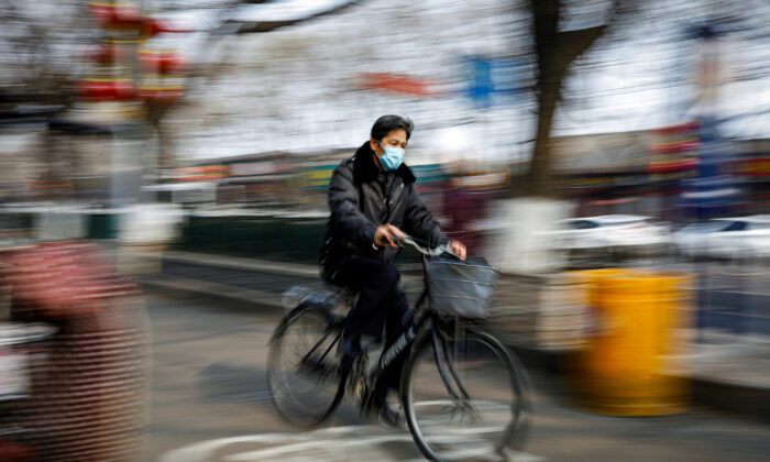A man wearing a face mask rides a bicycle, as the country is hit by an outbreak of the novel coronavirus, in Beijing, China on Feb. 12, 2020. (Carlos Garcia Rawlins/Reuters)