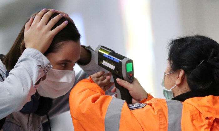 A worker checks the temperature of a passenger arriving into Hong Kong International Airport with an infrared thermometer, following the coronavirus outbreak in Hong Kong, China, on Feb. 7, 2020. (Hannah McKay/Reuters)
