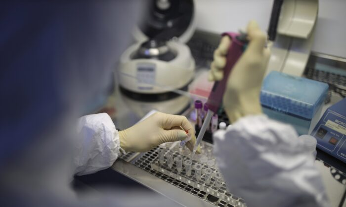 A medical staffer works with test systems for the diagnosis of coronavirus, at the Krasnodar Center for Hygiene and Epidemiology microbiology lab in Krasnodar, Russia on Feb. 4, 2020. (AP Photo)
