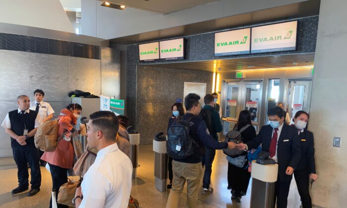 EVA Air employees are seen at Los Angeles International Airport (LAX) wearing masks, to prevent the coronavirus infection, COVID-19 in Los Angeles, California on Feb. 12, 2020. (Daniel Slim/AFP via Getty Images)