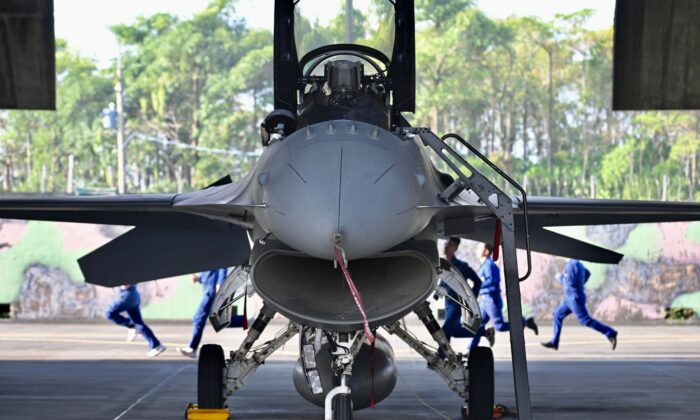 A group of Taiwan Air Force technicians run behind a US-made F-16V fighter jet during an exercise at a military base in Chiayi, southern Taiwan on Jan. 15, 2020. (Sam Yeh/AFP via Getty Images)