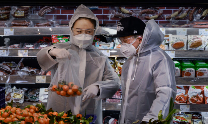 A Chinese couple wear plastic coats and protective masks as they shop for groceries at a supermarket in Beijing, China, on Feb. 11, 2020. (Kevin Frayer/Getty Images)