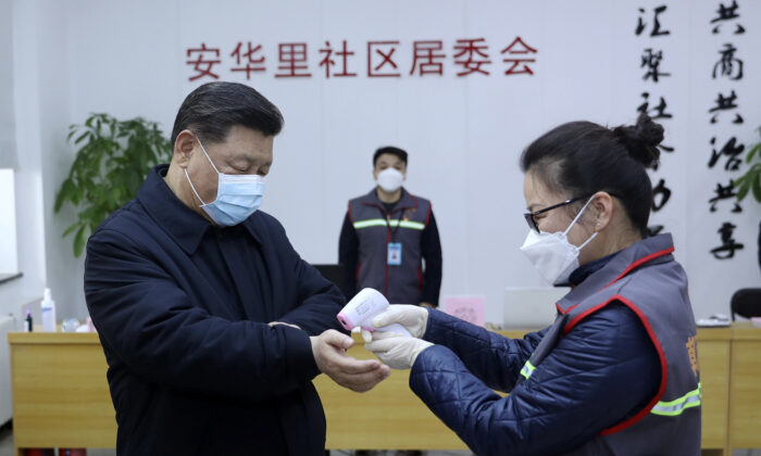 Chinese leader Xi Jinping, left, wearing a protective face mask, receives a temperature check while visiting a community health center in Beijing, China on Feb. 10, 2020. (Pang Xinglei/Xinhua via AP)