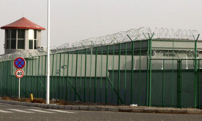 A guard tower and barbed wire-topped fences at an internment facility in the Kunshan Industrial Park in Artux, western China's Xinjiang region, on Dec. 3, 2018.  Ng Han Guan/AP Photo