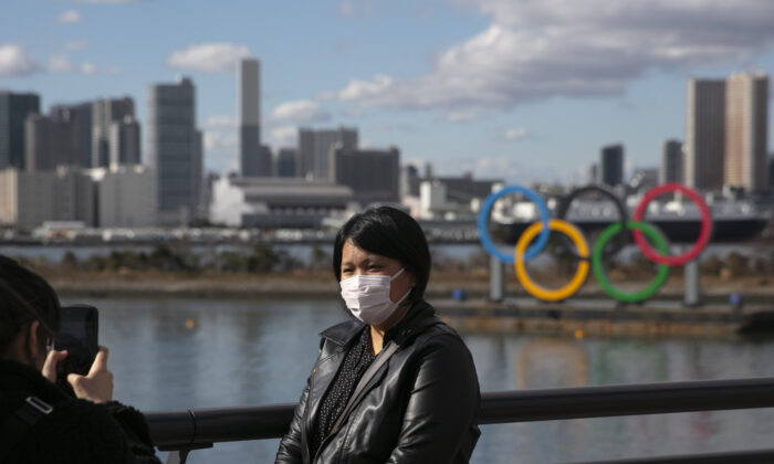 A tourist wearing a mask poses for a photo with the Olympic rings in the background, at Tokyo's Odaiba district, Japan, on Jan. 29, 2020. (Jae C. Hong/AP Photo/File)