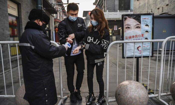 A Chinese security guard takes the temperature of a couple as they enter a nearly empty commercial street in Beijing, China, on Feb. 12, 2020. (Kevin Frayer/Getty Images)