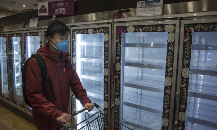 A resident passes by empty shelves in the supermarket in Wuhan, China on Feb. 12, 2020. (Getty Images)