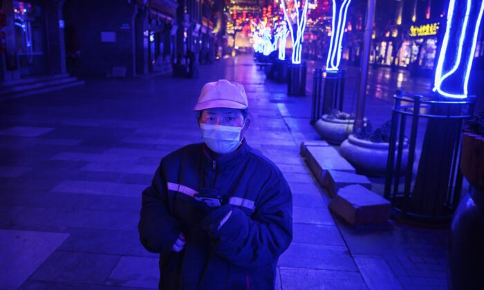 A Chinese worker stands in a nearly empty and shuttered commercial street in Beijing, China on Feb. 12, 2020. (Kevin Frayer/Getty Images)