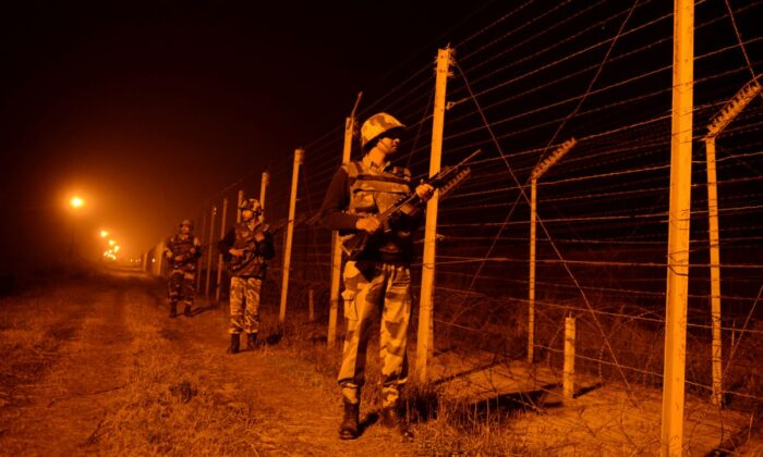 An Indian Border Security Force (BSF) soldiers patrol along the border fence at an outpost along the India-Pakistan border in Suchit-Garh, 36 kms southwest of Jammu on Jan. 11, 2013. (Tauseef Mustafa/AFP via Getty Images)