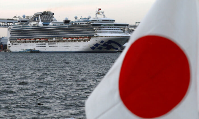 The cruise ship Diamond Princess is pictured beside a Japanese flag as it lies at anchor while workers and officers prepare to transfer passengers who tested positive for coronavirus, at Daikoku Pier Cruise Terminal in Yokohama, Japan, on Feb. 12, 2020. (Kim Kyung-Hoon/ Reuters/File Photo)