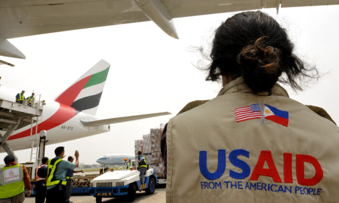 A US AID worker watches as relief supplies are unloaded at Manila's international airport on Oct. 13, 2009. (Jay Directo/AFP via Getty Images)