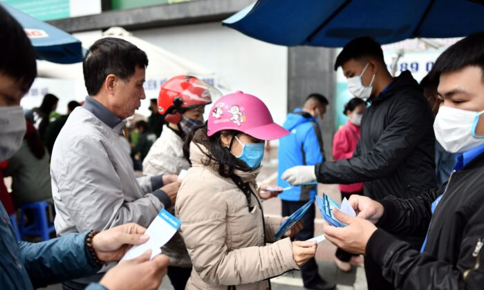 Vietnamese residents in line to receive free protective face masks at a makeshift distribution center amid concerns of the Novel Coronavirus outbreak, in Hanoi on Feb. 8, 2020. (Manan Vatsyayana/AFP/Getty Images)