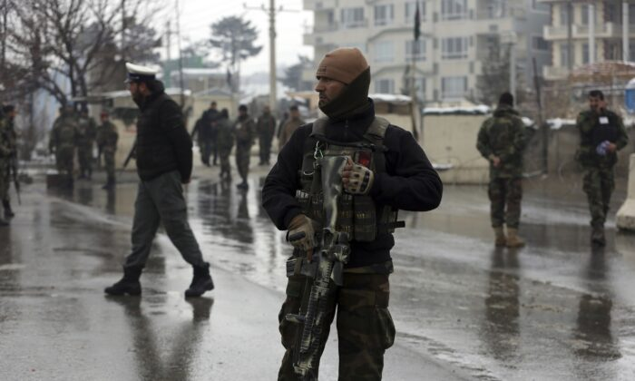 National army soldiers stand guard at the site of suicide attack near the military academy in Kabul, Afghanistan on Feb. 11, 2020. (Rahmat Gul/AP Photo)