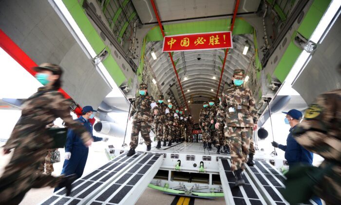 Medical personnel arrive with medical supplies in a transport aircraft of the Chinese People's Liberation Army (PLA) Air Force at the Wuhan Tianhe International Airport following the outbreak of the novel coronavirus in Wuhan, Hubei Province, China on Feb. 13, 2020. (China Daily via Reuters)