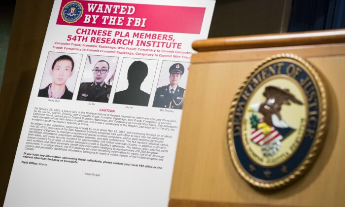 Signs that depict the four members of China's military indicted on charges of hacking into Equifax Inc. and stealing data from millions of Americans are seen shortly after Attorney General William Barr held a press conference at the Department of Justice on Feb. 10, 2020 in Washington. (Sarah Silbiger/Getty Images)