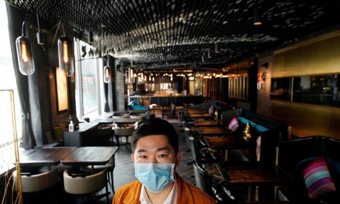 Bill Hu, founder and CEO of seul & SEUL restaurant, wears a mask and poses for pictures in downtown Shanghai, China, as the country is hit by an outbreak of a new coronavirus, on Feb. 12, 2020. (/Aly Song/Reuters)