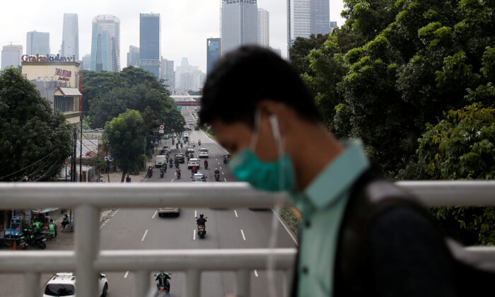 A man wearing protective mask uses his phone as he walks on a pedestrian bridge, following the outbreak of the new coronavirus in China, in Jakarta, Indonesia, on Feb. 13, 2020. (Willy Kurniawan/Reuters)