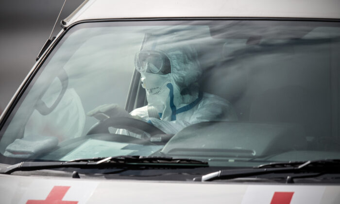 An emergency worker in protective clothing drives an ambulance carrying a person diagnosed with COVID-19 in Yokohama, Japan, on Feb. 13, 2020. (Carl Court/Getty Images)