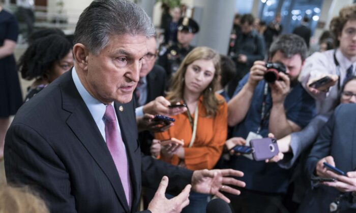 Senator Joe Manchin (D-W.Va.) speaks to the press near the Senate subway following a vote in the Senate impeachment trial that acquitted President Donald Trump of all charges in Washington on Feb. 5, 2020. (Sarah Silbiger/Getty Images)