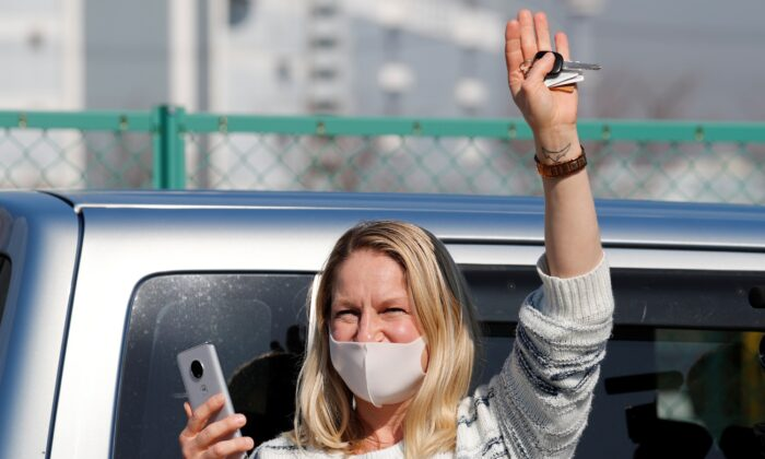 A woman waves from outside Daikoku Pier Cruise Terminal as she communicates via phone with a passenger (not pictured) standing o­n the balcony of a cabin o­n the cruise ship Diamond Princess, as the vessel's passengers continue to be tested for coronavirus, in Yokohama, south of Tokyo, Japan o­n Feb. 13, 2020. (Kim Kyung-Hoon/Reuters)