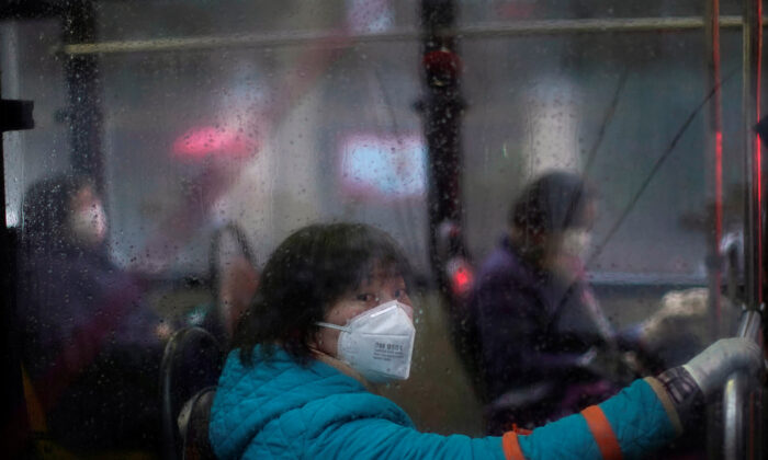 Women wearing masks are seen on a bus in downtown Shanghai, China, as the country is hit by an outbreak of a new coronavirus on Feb. 13, 2020. (Aly Song/Reuters)