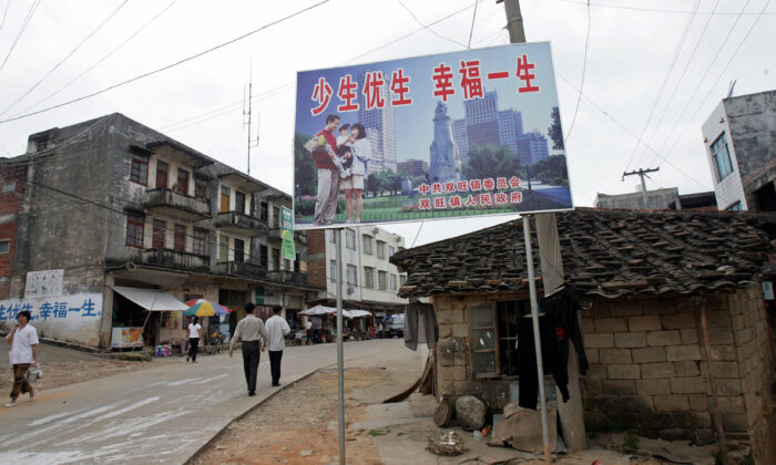 """A """"one-child"""" policy billboard saying, """"Have less children, have a better life,"""" greets residents on the main street of Shuangwang, southern China's Guangxi region in May 2017. (Goh Chai Hin/AFP via Getty Images)"""