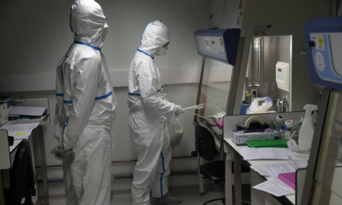 French lab scientists in hazmat gear inserting liquid in test tubes manipulate potentially infected patient samples at Pasteur Institute in Paris on Feb. 6, 2020. (Francois Mori/AP Photo)