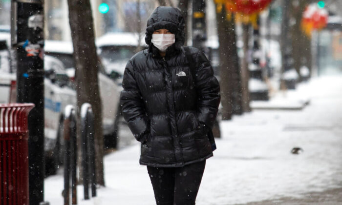 People walking through Chinatown, near West Cermak and South Wentworth, brave snowfall and temperatures that plummeted to the teens, on Feb. 13, 2020 in Chicago. (Ashlee Rezin Garcia/Chicago Sun-Times via AP)
