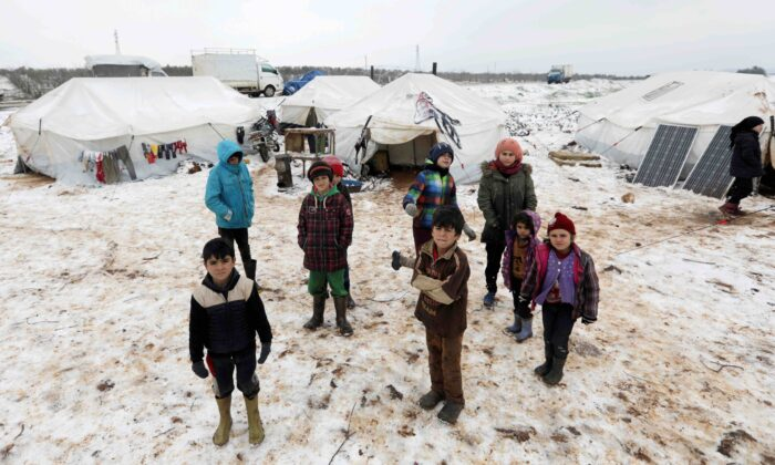 Internally displaced children stand on snow near tents at a makeshift camp in Azaz, Syria, on Feb. 13, 2020. (Khalil Ashawi/Reuters)