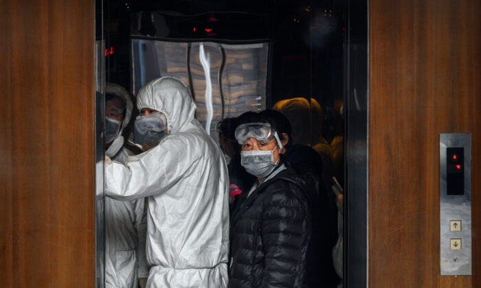 Chinese workers wearing protective suits stand in an elevator at a mall in Beijing, China, on Feb. 9, 2020. (Kevin Frayer/Getty Images)