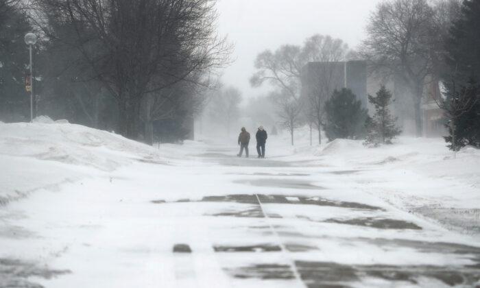 A pair of pedestrians make their way across campus at Northern State University in South Dakota on Feb. 12, 2020. (American News via AP/John Davis)